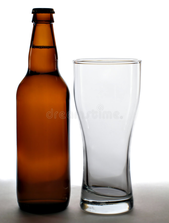 Beer bottle and empty glass. Isolated against white background stock photography