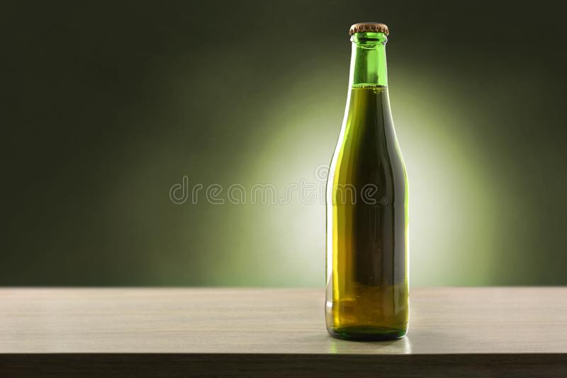 Beer bottle filled and closed on wood table green background royalty free stock images