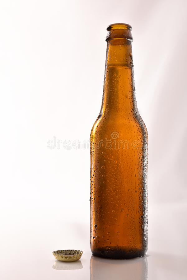 Beer bottle filled and open on glass table black background royalty free stock photo
