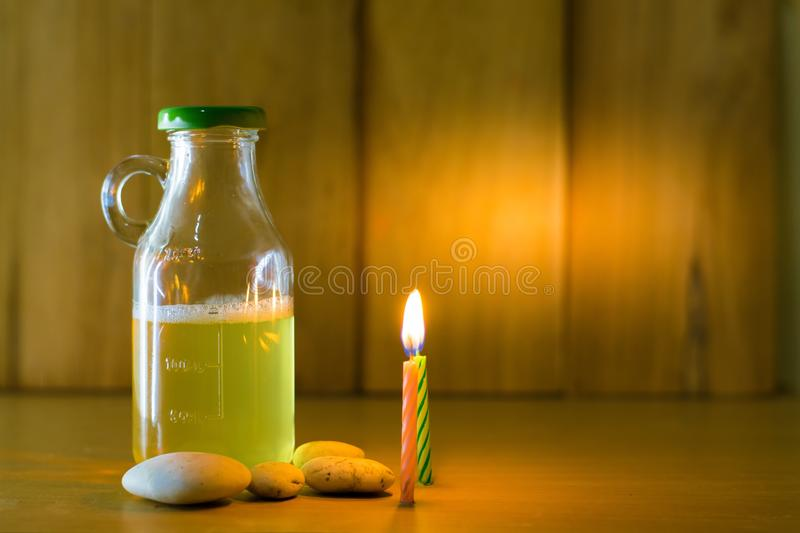 Beer bottle and fire of candles put on wood with wooden background using wallpaper for party at night. Beer bottle put on wood with wooden background using royalty free stock image