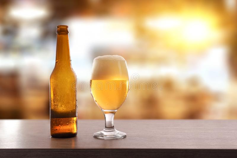 Beer bottle and glass cup on table in leisure place stock photography