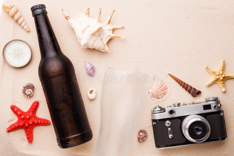 Beer bottle and glass on a sandy beach. royalty free stock images