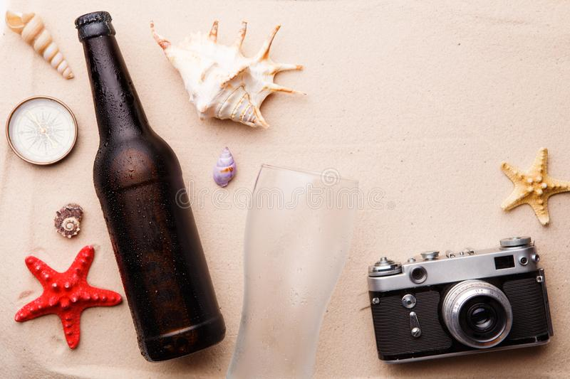 Beer bottle and glass on a sandy beach. royalty free stock image