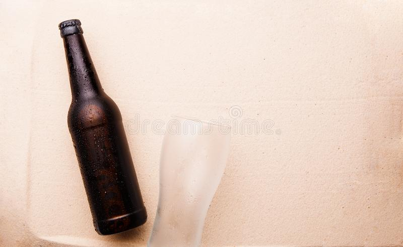 Beer bottle and glass on a sandy beach. royalty free stock photography