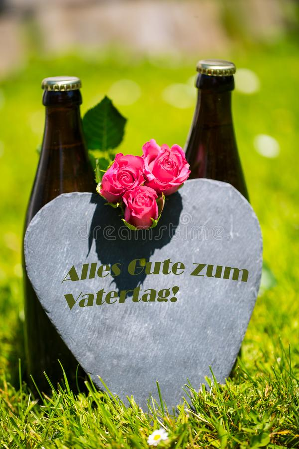 Beer bottle with heart and roses for Father`s Day. Flower royalty free stock photo