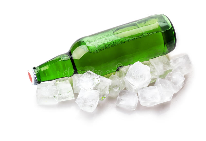 Beer bottle in ice cubes. Isolated on white background stock photography