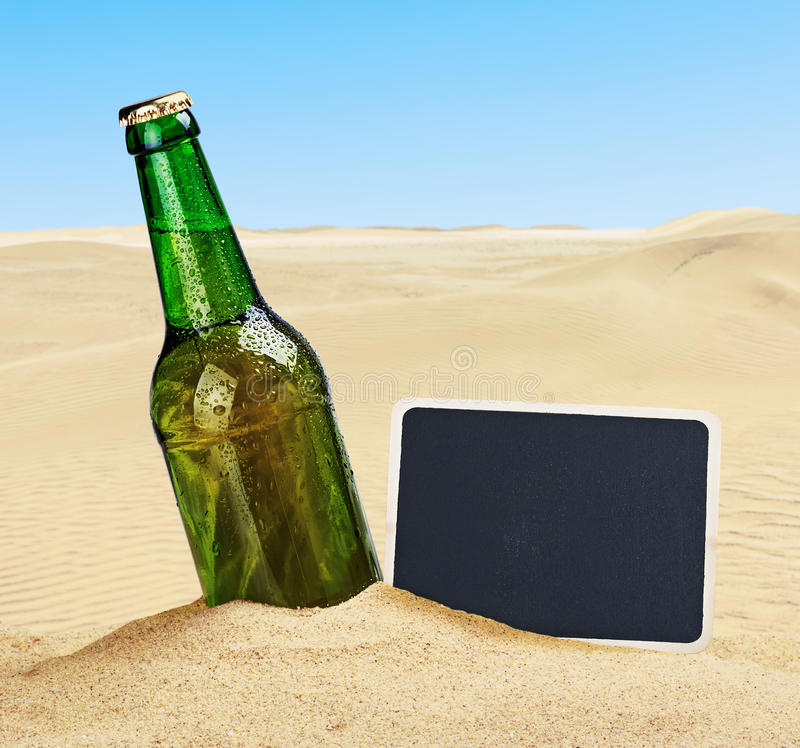 Free Beer Bottle In The Sand In The Desert And The Blackboard Stock Image - 42246251