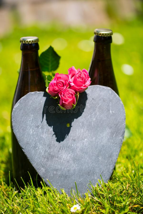 Beer bottle lying with roses for Father`s Day stock photo