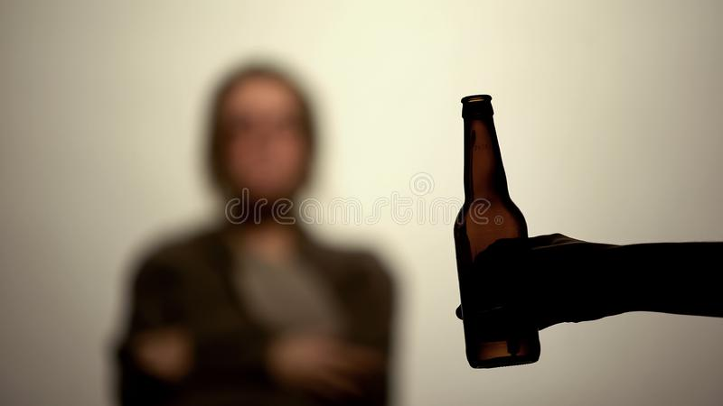 Beer bottle in male hand white background, alcohol offer, rehabilitation center royalty free stock photography