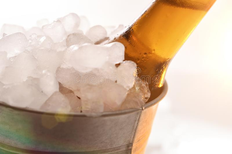 Beer bottle in metal bucket full of ice cubes detail royalty free stock photography