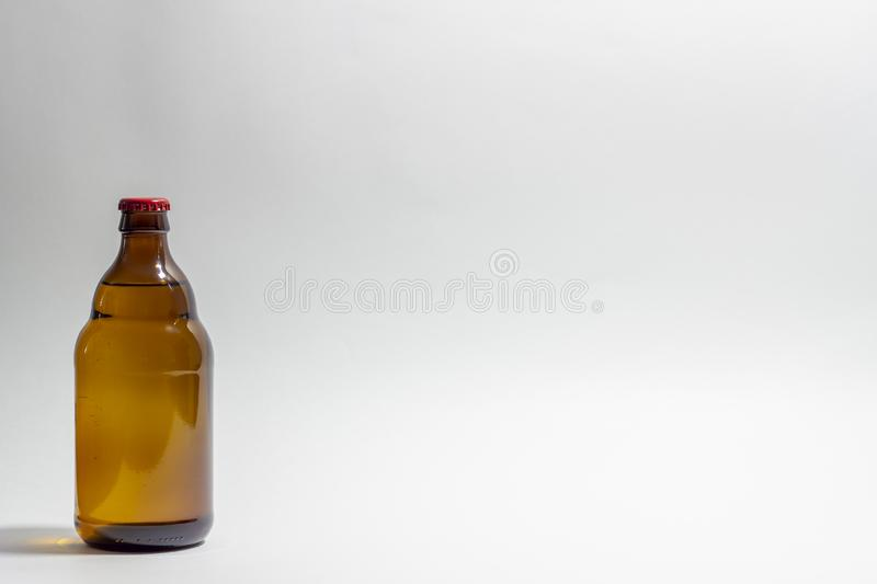 Beer bottle with a red cork on a gray background. Design. Minimalism. Creative idea. Mock-up royalty free stock photos