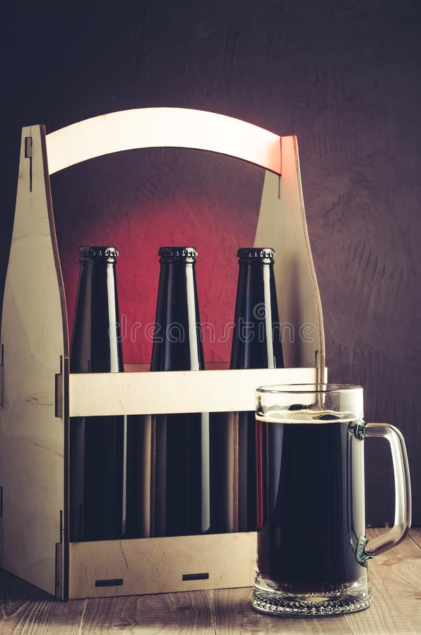 beer bottles case and mug on a red light background/beer bottles case and mug on a red light background. Selective focus stock photos