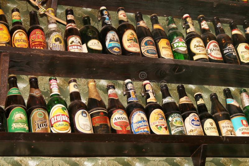 The beer bottles collection. Zrenjanin, Serbia – 22 January, 2019: The beer bottles collection at the wall in a popular pub stock image