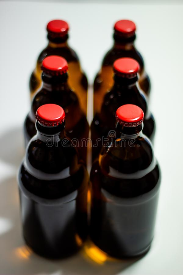 Beer bottles with a red cork on a gray background. Top view. Design. Minimalism. Creative idea. Mock-up. Drink, lager, glass, beverage, brown, ale, clean royalty free stock photography