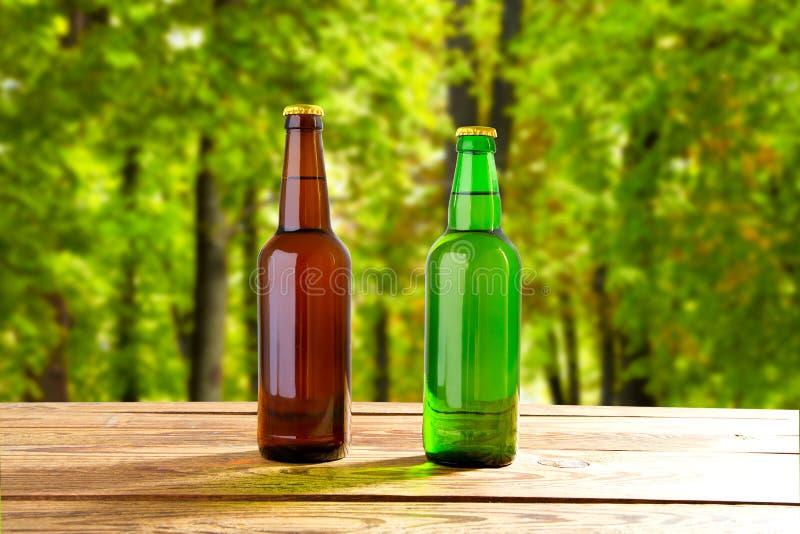 Beer bottles on table on blurred park background,coloured bottle. Beer bottles on table on blurred park background, coloured bottle stock photo