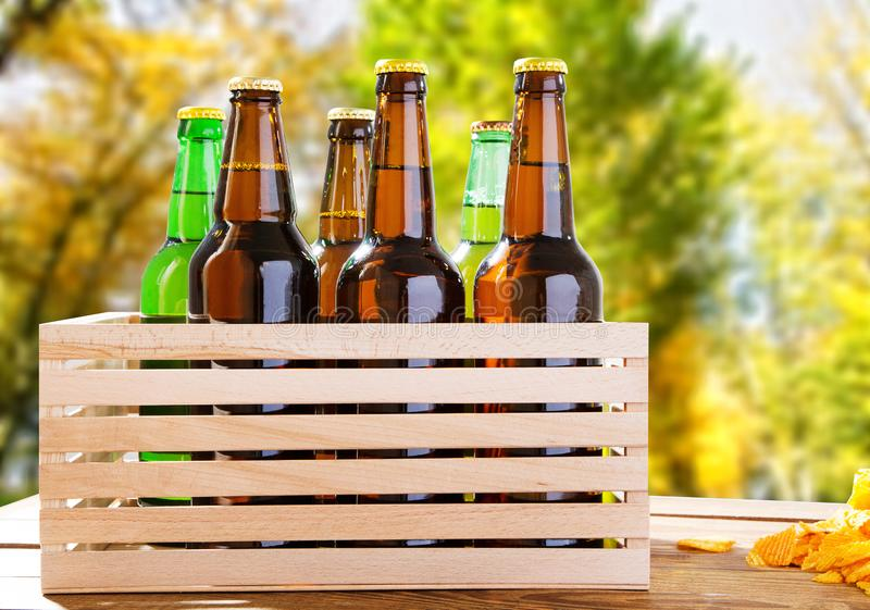 Beer bottles on wooden table with blurred forrest on background, coloured bottle, food and drink concept,selective focus,copy spac. E stock photo