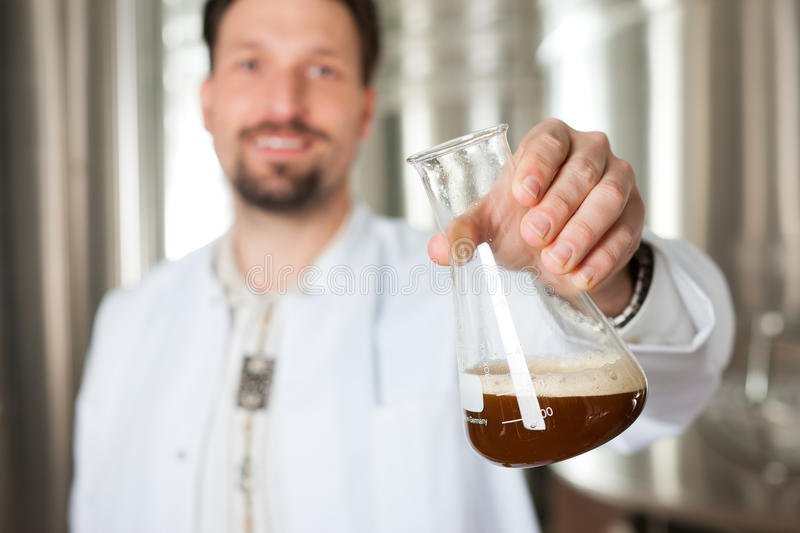 Beer brewer in his brewery examining. Brewer standing in his brewery and is examining the beer for its purity royalty free stock photo