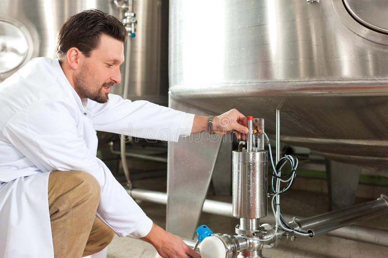 Beer brewer in his brewery. At food tank royalty free stock photo