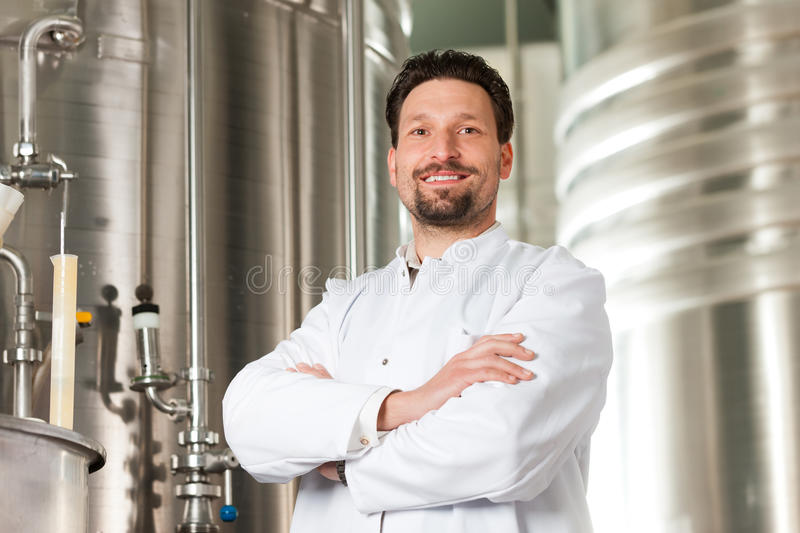 Beer brewer in his brewery. Brewer standing in his brewery in front of a stainless copper fermenter stock photo