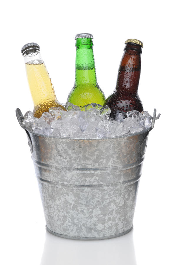 Beer Bucket with three beers. Three Different Beer Bottles in bucket of ice with condensation vertical composition over white background royalty free stock photo