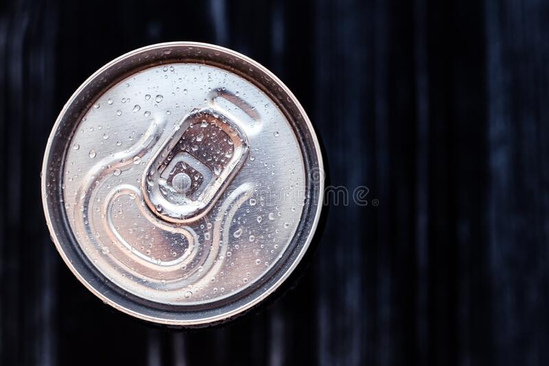 Beer can with condensation on black background. Aluminium can of drink with water drops, refrigerated cola can, top view. Text. Space stock images