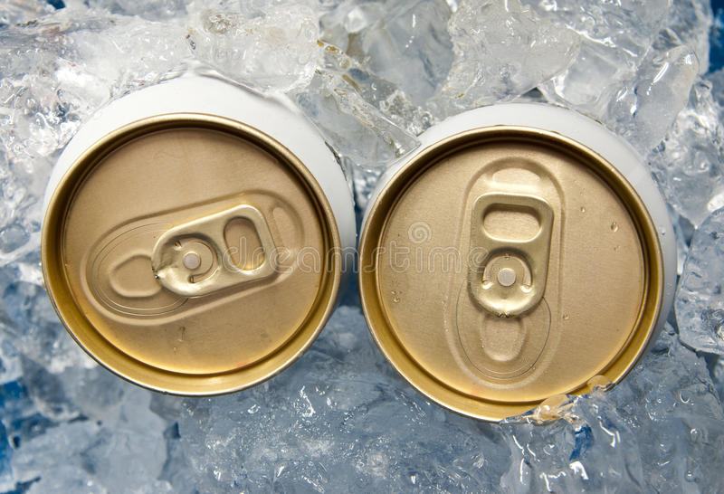 Beer cans and ice. Two aluminum beer cans and ice royalty free stock images