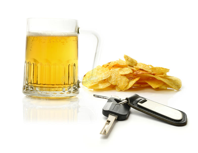 Beer and car keys. Studio macro of pint of beer, scattered potato chips (crisps) and car keys on a white surface. Concept image for drink driving. Copy space royalty free stock images