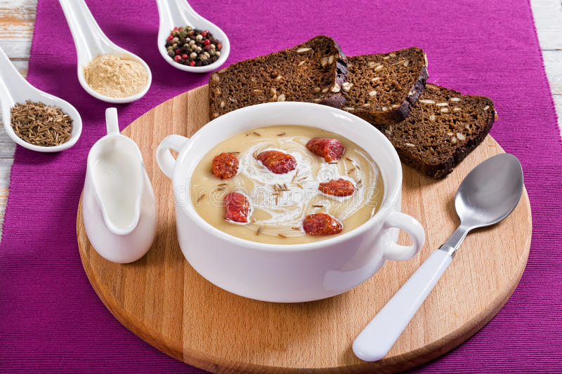 Beer and Cheddar cream Soup with Kielbasa Sausage. Sprinkled with cumin in white soup cup on round board with rye bread with seeds, close-up, view from above royalty free stock photos