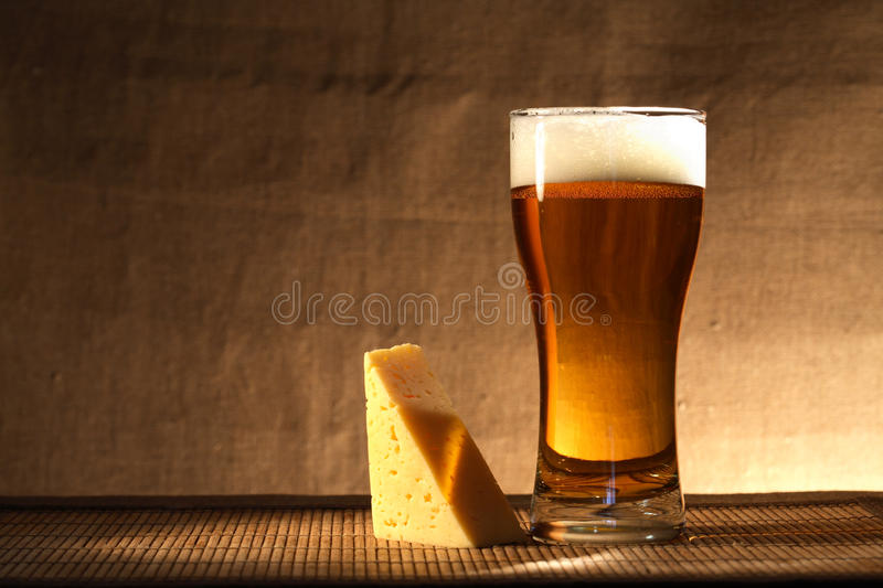 Beer And Cheese. Glass of freshness beer with foam near cheese on gray canvas background stock image