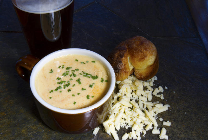 Beer Cheese Soup with Chives. Crock of beer cheese soup with chives on slate table accompanied by glass of beer, popover and shredded cheese royalty free stock photo