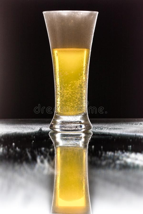 Beer. Cold Craft light Beer in a glass with water drops. Pint of Beer close up isolated on black color background. Border design royalty free stock photography