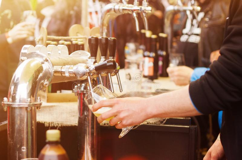 Beer cranes and blurred people in the street food festival. Beer cranes, bartender`s hand with a glass and blurred people in the street food festival royalty free stock images