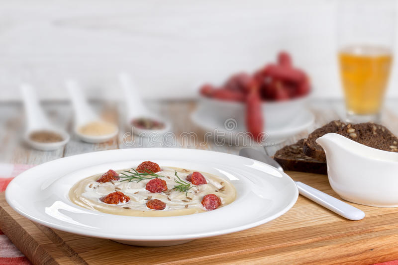Beer and cream Soup with Kielbasa Sausage, dill. and cheese. Delicious Beer and cream spicy Soup with Kielbasa Sausage, dill. and cheese in wide rim plate on royalty free stock images