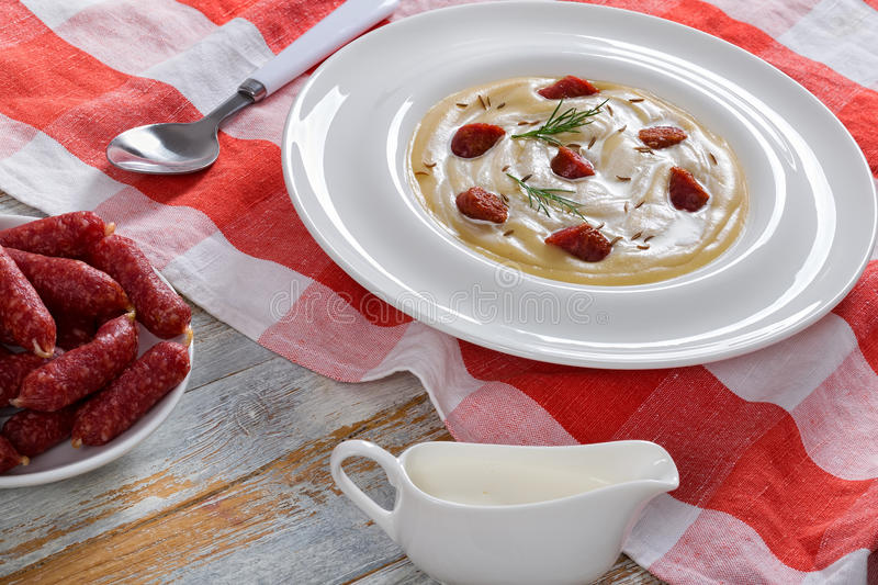 Beer and cream spicy winter Soup with Kielbasa Sausage. Delicious Beer and cream spicy winter Soup with Kielbasa Sausage, dill. and cheese sprinkled with caraway royalty free stock photo