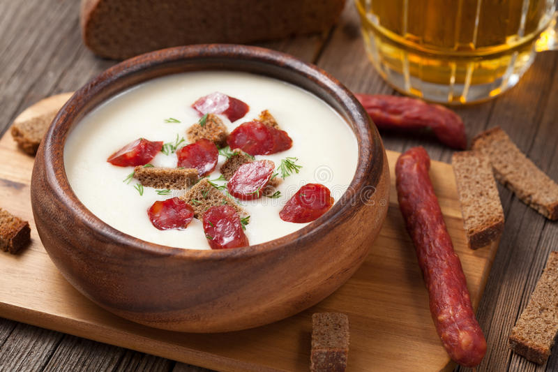 Beer cream white soup with sausages and croutons. On vintage background royalty free stock image