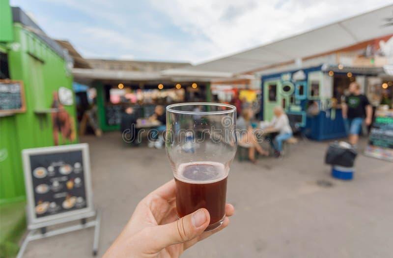 Beer drinkers on street food market of Copenhagen, Denmark. Leisure in Scandinavia with drinks and food of city market. Beer drinkers on street food market of stock photography