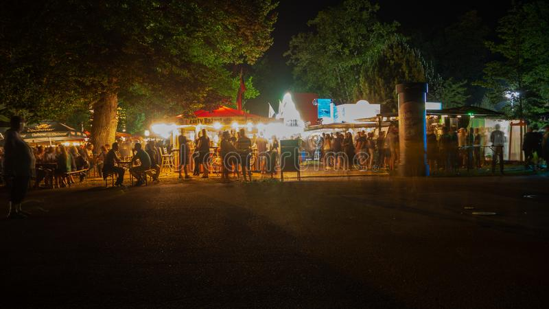 Karlsruhe, Germany - 30 August 2019: beer festival at palace park at night -BIERBOERSE. Beer festival at palace park at night - people celebrating saturday night royalty free stock images