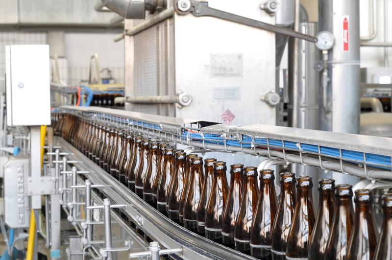 Beer filling in a brewery - conveyor belt with glass bottles stock images