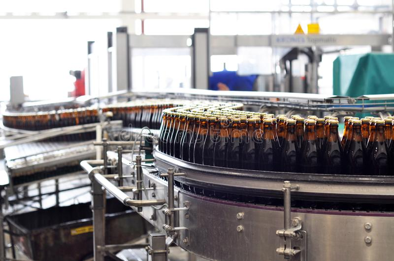 Beer filling in a brewery - conveyor belt with glass bottles stock image