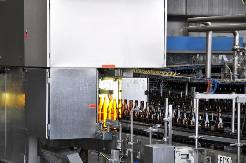 Beer filling in a brewery - conveyor belt with glass bottles royalty free stock image