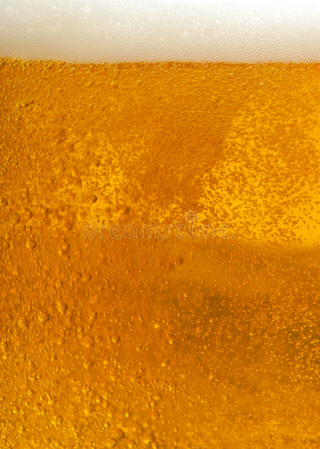 Beer foam. Vertical beer foam texture close-up. Fresh beer in a very large glass royalty free stock image