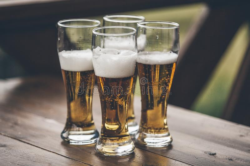 Beer with foam light tall boys standing on a wooden table closeup stock photography