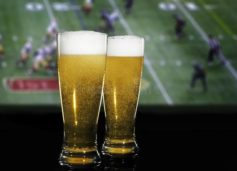 Beer Football. Two filled beer glasses on black surface with American football game on TV screen blurred in background. A concept for enjoying beer during