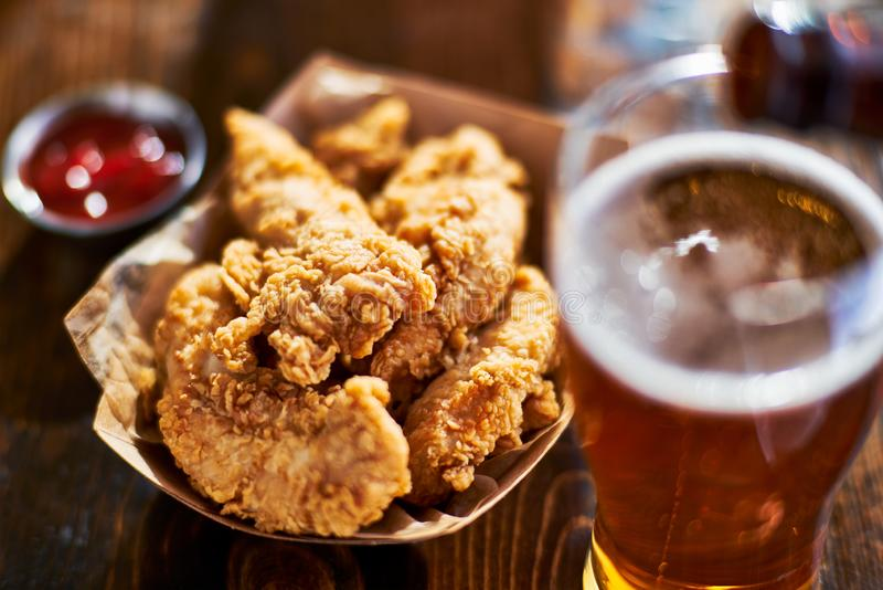 Beer and fried chicken tenders. Shot with selective focus stock photography