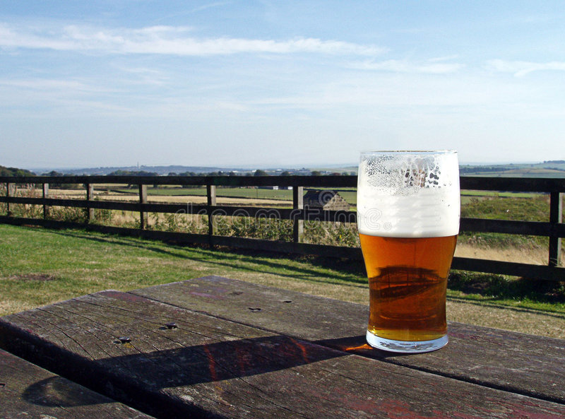 Beer Garden. A pint of English Beer on a typical pub beer garden table, overlooking a typical english countryside landscape