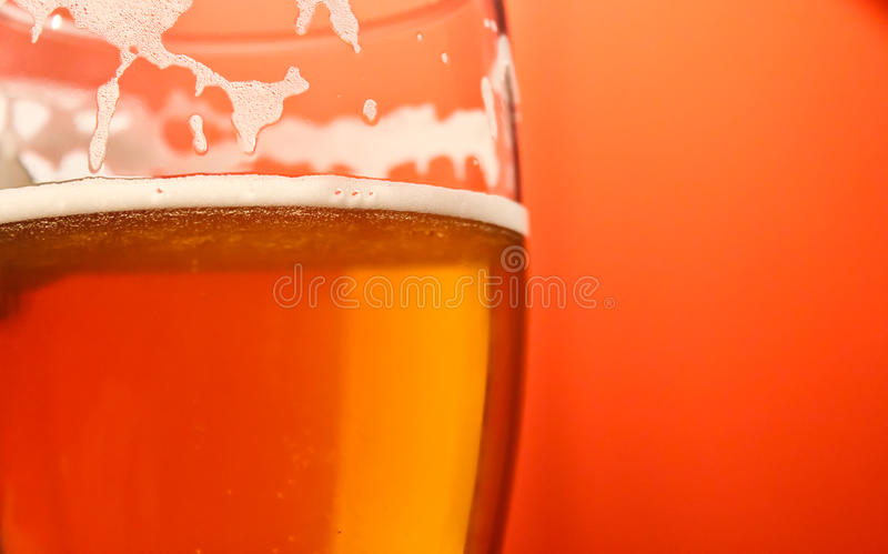 Beer Glass. Macro with orange backdrop royalty free stock images