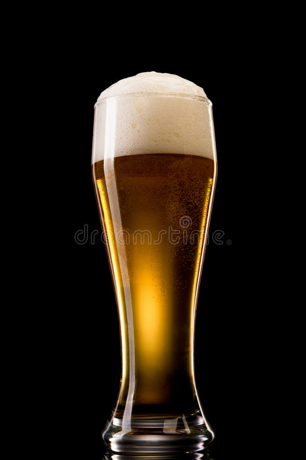 Beer into glass on a black royalty free stock images
