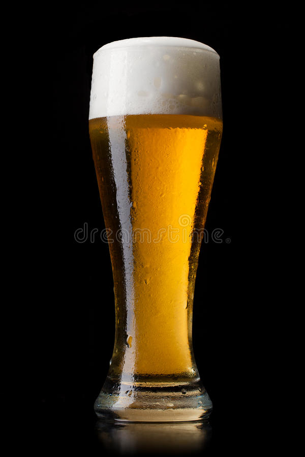 Beer into glass on a black stock photos