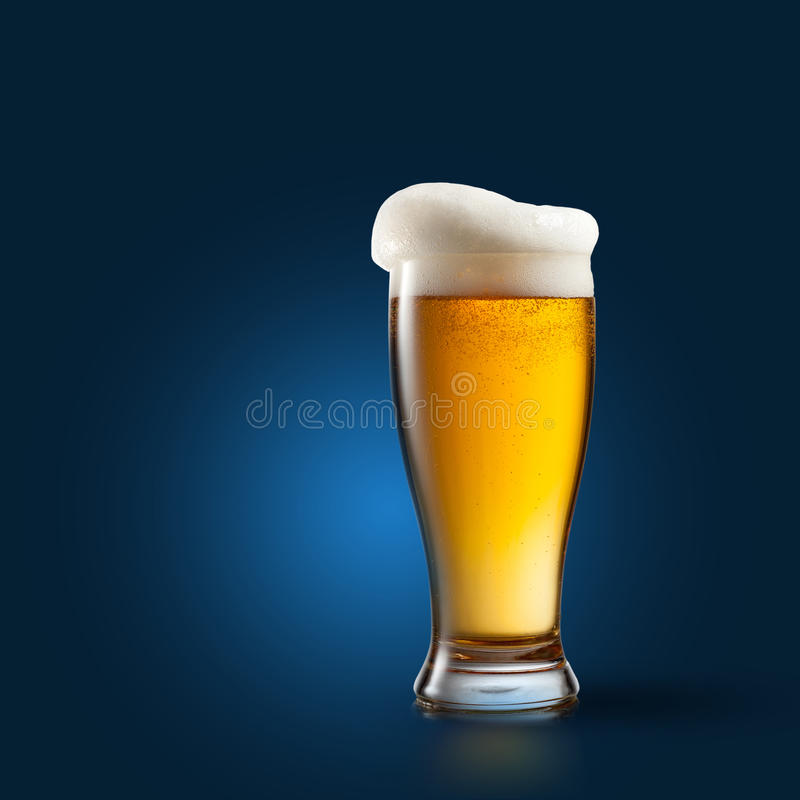Beer in glass on blue stock images