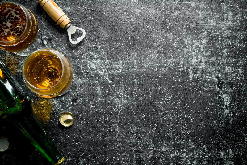 Beer by the glass and bottle. On black rustic background royalty free stock image